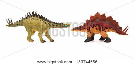 yellow huayangosaurus and red stegosaurus toys on a white background