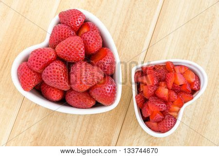 Whole and diced strawberries in two white heart shaped bowls