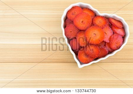 Sliced strawberries in a white heart shaped bowl
