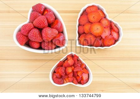 Whole, sliced, and diced strawberries in three white heart shaped bowls