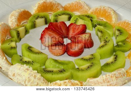 Strawberry, Kiwi, Orange, Tangerine fruit platter. Organic fruits on the white plate. Vitamin C Fruits