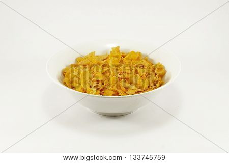Bowl of cornflakes on colorful table mat; white background