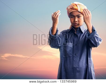 muslim child praying for Allah muslim God on the sunset sky background