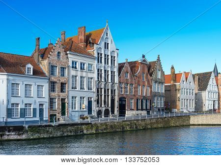 Bruges - circa February 7 of 2016, Belgium: View with canal and varicolored traditional brick houses in popular belgian city of Bruges