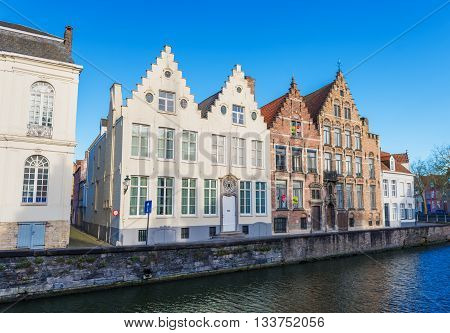 Bruges (Brugge) - circa February of 2016, Belgium:  Typical belgian street with traditional houses and water canal (Spinolarei street)