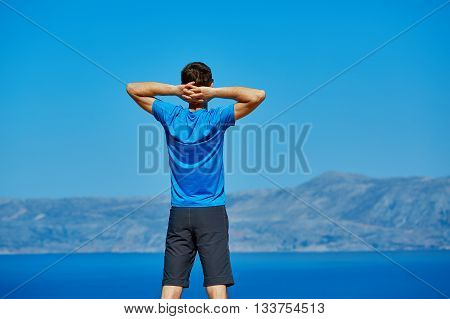 young man doing sports workout on the cliff against sea and blue sky at early morning