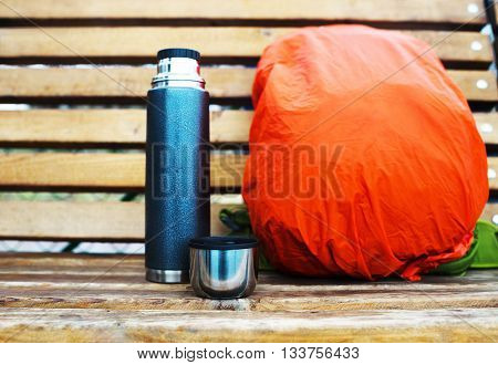 Horizontal thermos with backpack on bench bokeh background