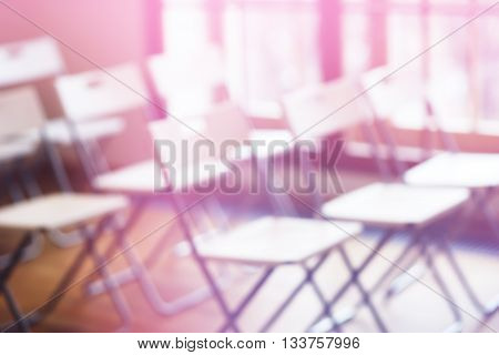 Classroom with empty chairs and pink bokeh background