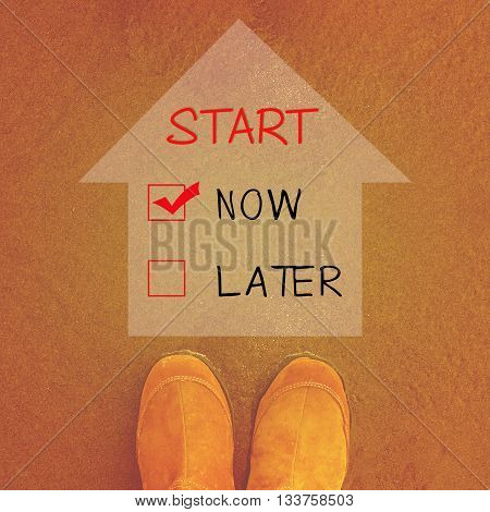Start now or later words on sand background