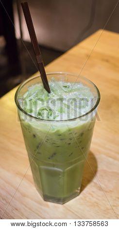 Ice milk green tea on wooden table stock photo