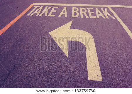 Take a break word on street with turn left arrow