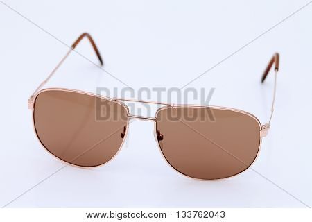 Brown aviator style sunglasses on white background