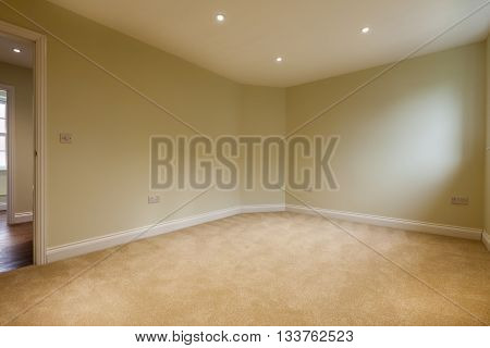 Empty apartment bedroom with Sympathetic dimmed lighting carpet and doorway to hall