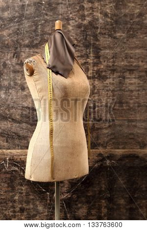 A piece of grain leather, tape measure pinned on a mannequin in studio fur