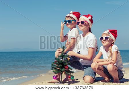 Three happy children playing on the beach at the day time. Concept of Happy New Year.