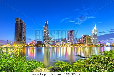 Ho Chi Minh City, Vietnam - June 9th, 2016: Beauty skyscrapers along river light smooth down river, foreground drifting hyacinth patches adorn country urban development in Ho Chi Minh City, Vietnam
