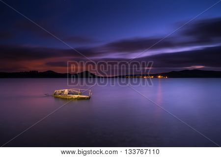 Sunken boat in the lake at night