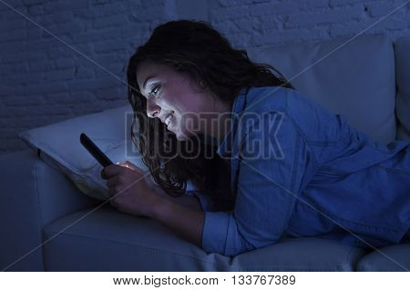 young beautiful woman lying on home sofa couch using mobile phone texting or enjoying app fully concentrated and focused at night in internet and social network addiction smiling happy