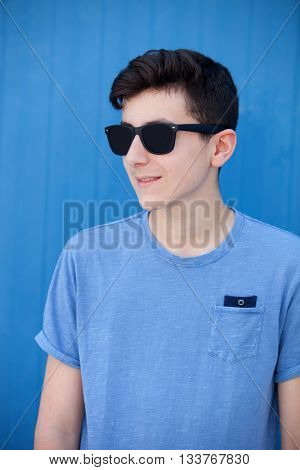 Portrait of a teenager rebellious man with sunglasses on a blue background