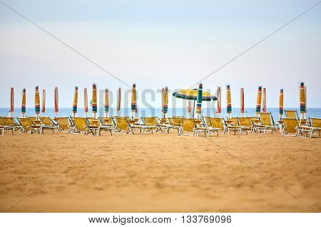 Empty Sun Lounges And Closed Parasols On The Beach