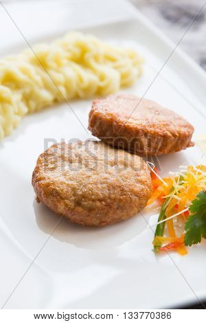 Meat cutlets with smashed potatoes on a white plate