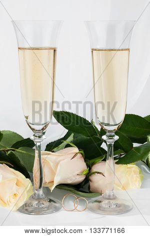 Wedding background with two glasses of champagne ring and rose on white background.