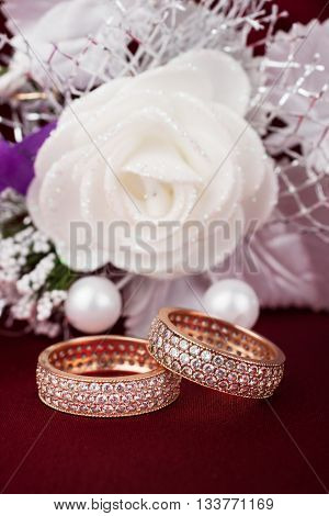 Wedding background with two rings and rose on red background