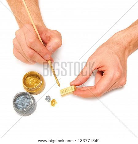 Man makes a gold bar. Bullion brush paint hands isolated on white
