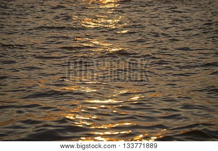 Background photo, sun glare on dark sea water with wave pattern, select focus
