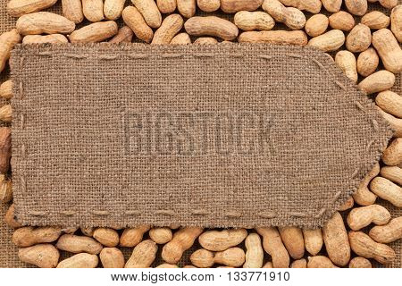 Pointer of burlap lying on a peanuts background with place for your text