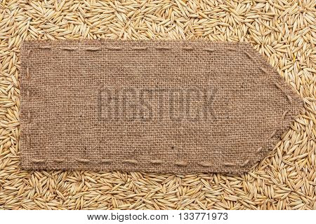 Pointer of burlap lying on a oats background with place for your text