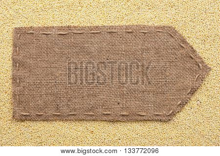 Pointer of burlap lying on a millet background with place for your text