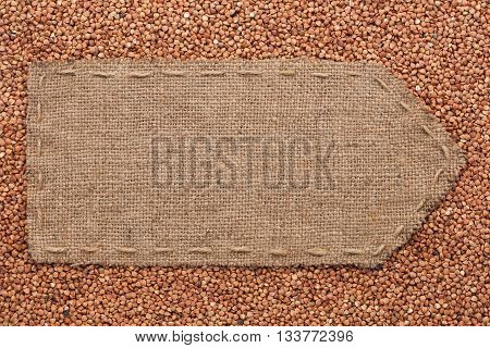 Pointer of burlap lying on a buckwheats background with place for your text