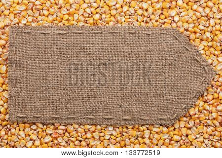 Pointer of burlap lying on a corn background with place for your text