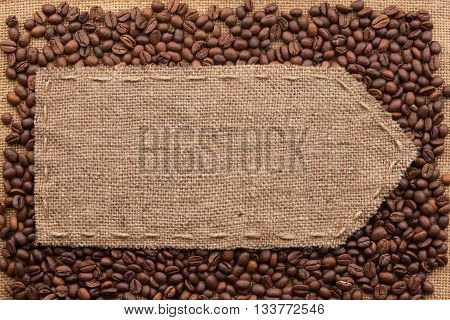 Pointer of burlap lying on a coffee beans background with place for your text