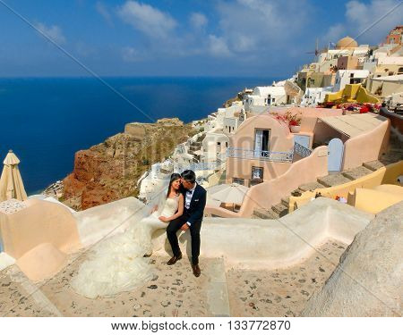 Oia, Greece - June 10, 2015: Santorini - The Oia, Greece - June 10, 2015: Santorini - The newlyweds on beautiful terrace with sea view on Santorini island, Oia, Greece.