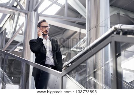 Man on smart phone - young businessman in airport. Handsome serious men wearing suit jacket indoors.