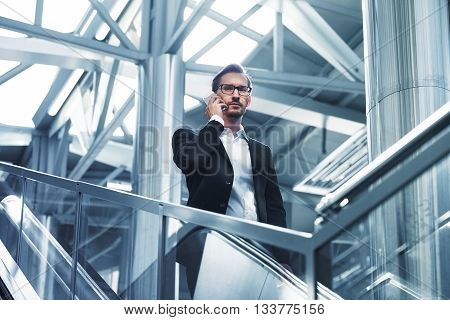 Man on smart phone - young businessman in airport. Handsome serious men wearing suit jacket indoors. Toned photo