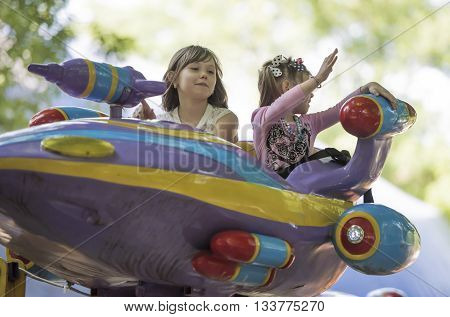 Rostov-on-Don Russia- May 29 2016:Two girls with admiration go for a drive on the carousel in the park named after Ostrovsky