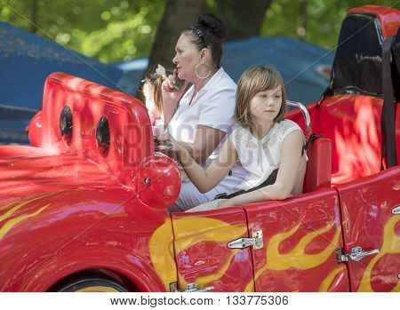 Rostov-on-Don Russia- May 29 2016: Girl and grandmother talking on the phone ride in the car- rockin in the park named after Ostrovsky