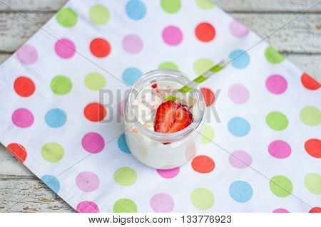 jar of yogurt and strawberry with multi-colored cloth on wooden table