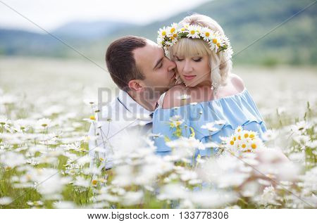 A young couple,pregnant woman,the blonde in the sundress blue,ears are silver earrings,and on her head a wreath of white daisies,a man, a brunette with short hair in a shirt with short sleeves,spend time on the blossoming white flowers meadow
