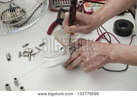 person repair the fan, damaged fan motor does not work
