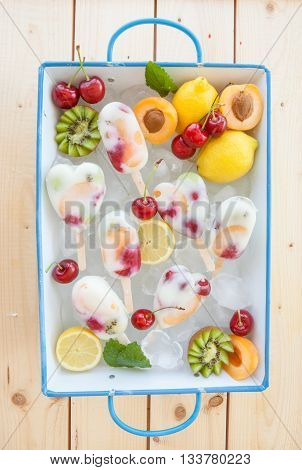 Homemade frozen popsicles with fresh fruits and yogurt