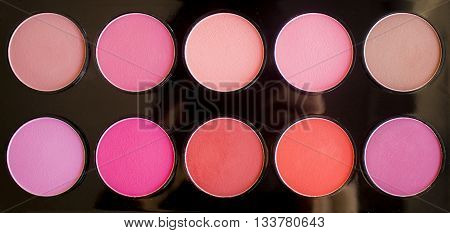 Colorful blush, shadows set on black background. Dry textured palette of professional cosmetics.