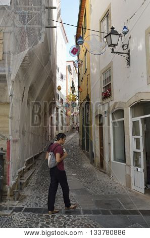 COIMBRA, PORTUGAL - AUGUST 3, 2016: A few people in a narrow cobble street in the historical centter of Coimbra Portugal