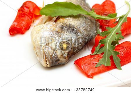 tasty Roasted fish with red garnish on plate