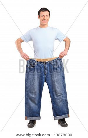 Full Length Portrait Of A Weight Loss Male Showing His Old Jeans