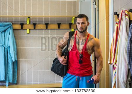 Portrait of handsome man in dressing room with sportsbag
