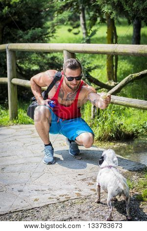 Portrait of handsome muscular man in sunglasses with bag playing ball with pet dog in summer park